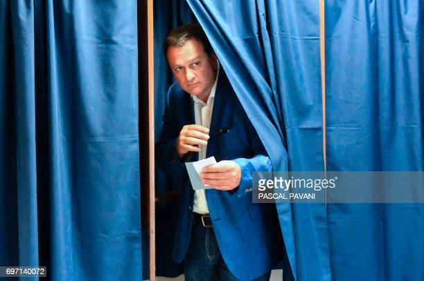 Louis Aliot candidate of the far right National Front party in the 2nd constituency of the Pyrenees orientales walks out a polling booth as he votes...