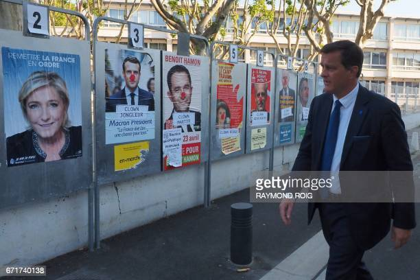 Louis Aliot one of the vicepresidents of the French farright National Front party walks past electoral posters in Perpignan on April 23 during the...