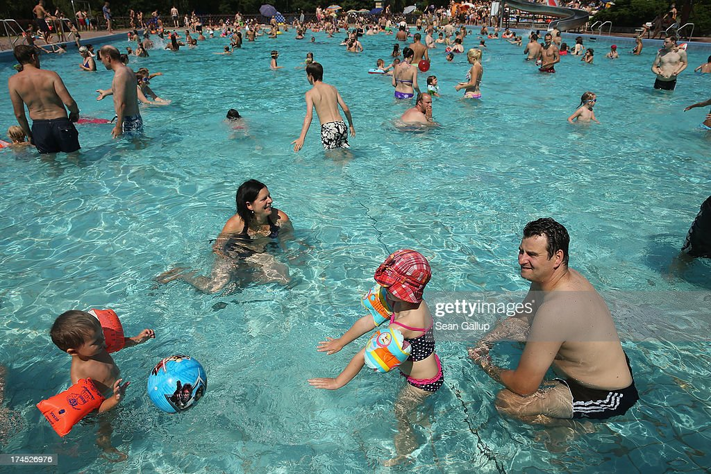 Louis and his sister Clara cool off in the shallow pool with their parents at the Freibad Kiebitzberge outdoor public pool on July 27 2013 in Berlin...