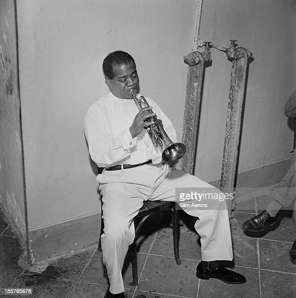 Louis Armstrong US jazz trumpeter and singer sitting in a chair against a wall playing the trumpet in Rome Italy 1959