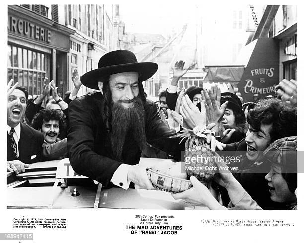 Louis De Funes hands out fruit in a scene from the film 'The Mad Adventures Of 'Rabbi' Jacob' 1973