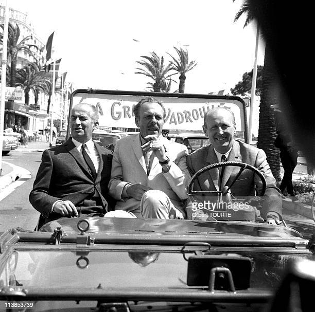 Louis de Funes Terry Thomas and Andre Bourvil in a jeep on the croisette during the Cannes International Film Festival in 1966