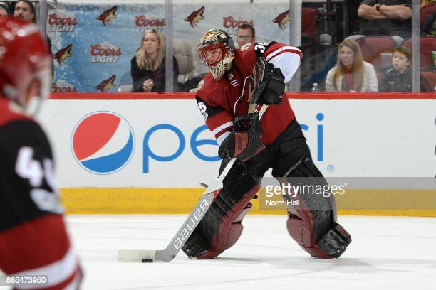Louis Domingue of the Arizona Coyotes passes the puck up ice against the Chicago Blackhawks at Gila River Arena on October 21 2017 in Glendale Arizona
