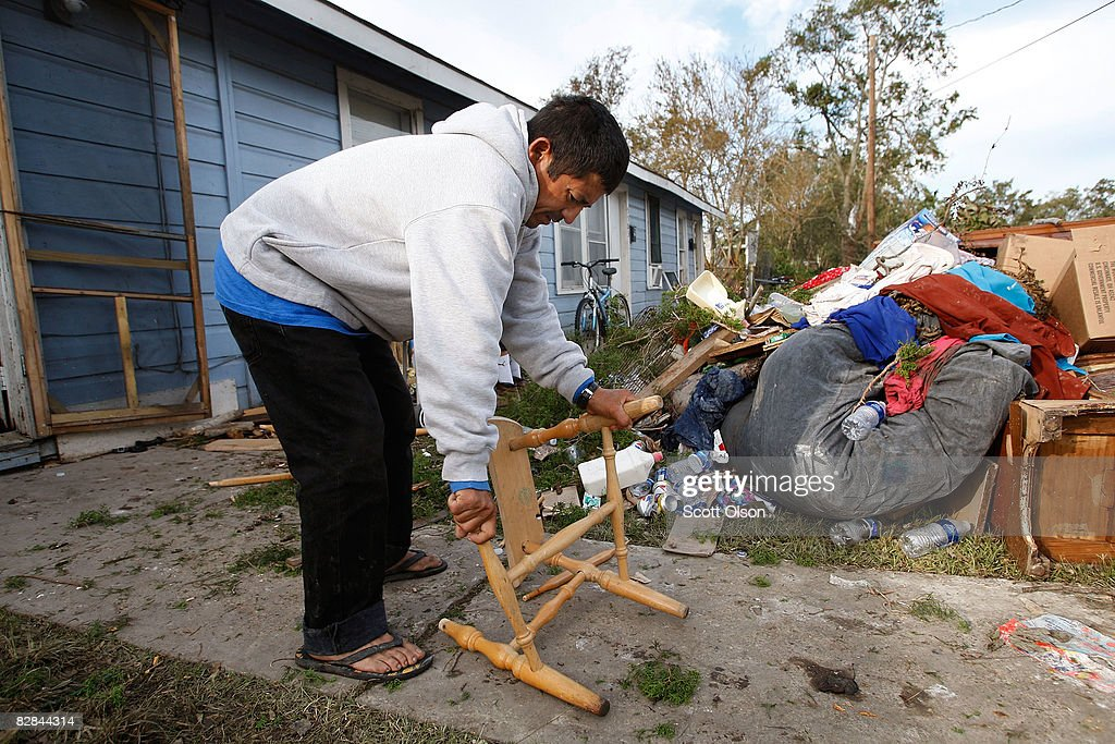 Louis Enrique Sarmiento breaks apart a flooddamaged chair to use for firewood to cook breakfast on a grill following Hurricane Ike September 16 2008...