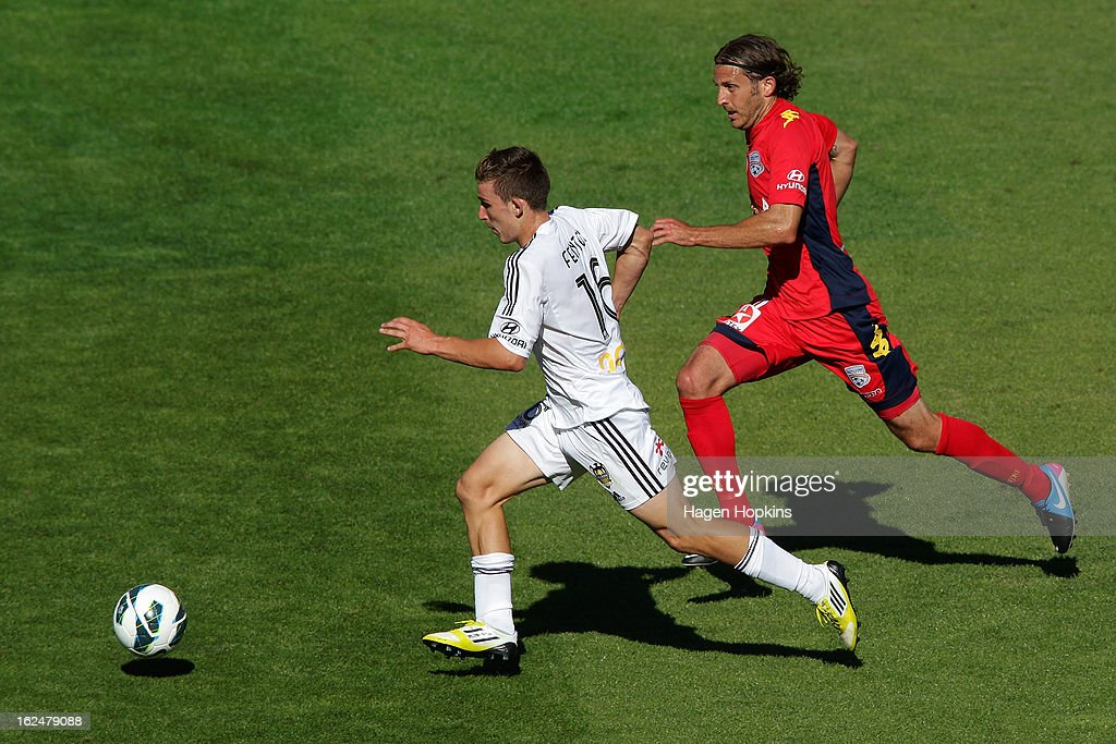 Louis Fenton of the Phoenix makes a break away from Jon McKain of Adelaide during the round 22 A-League match between the Wellington Phoenix and Adelaide United at Westpac Stadium on February 24, 2013 in Wellington, New Zealand.
