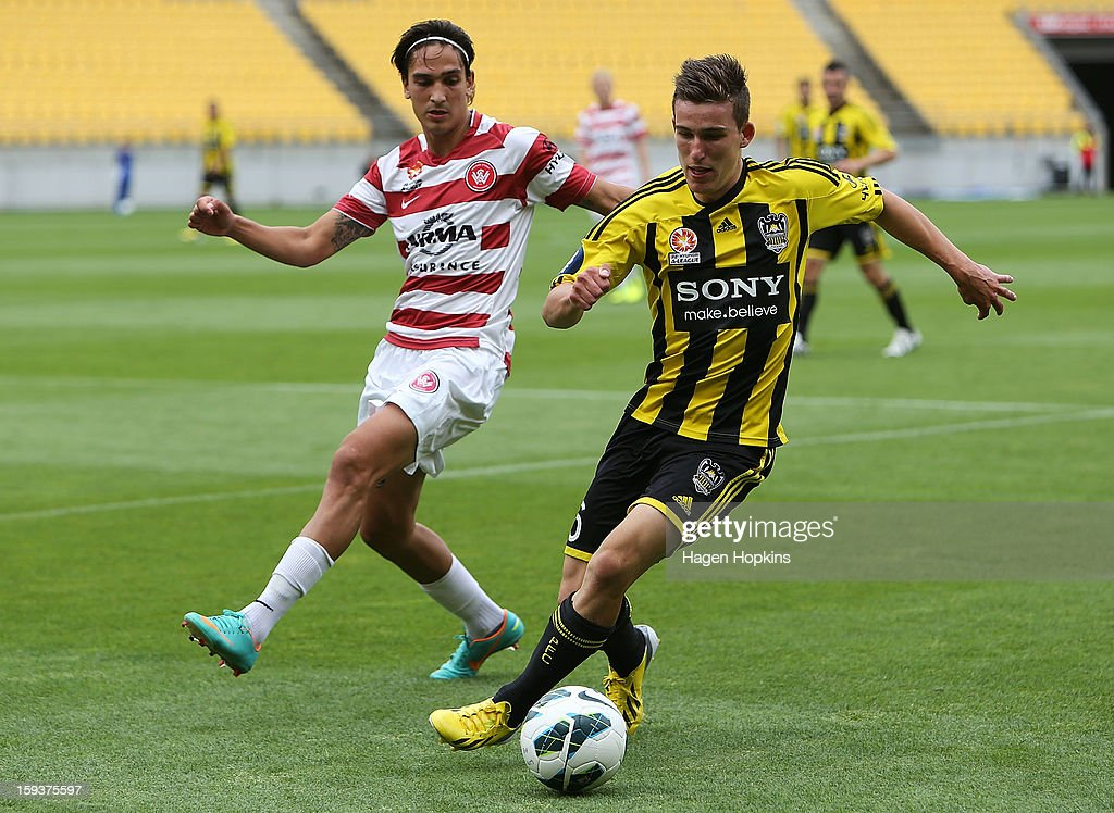 Louis Fenton of the Phoenix runs the ball under pressure from Jerome Polenz of the Wanderers during the round 16 A-League match between the Wellington Phoenix and the Western Sydney Wanderers at Westpac Stadium on January 13, 2013 in Wellington, New Zealand.