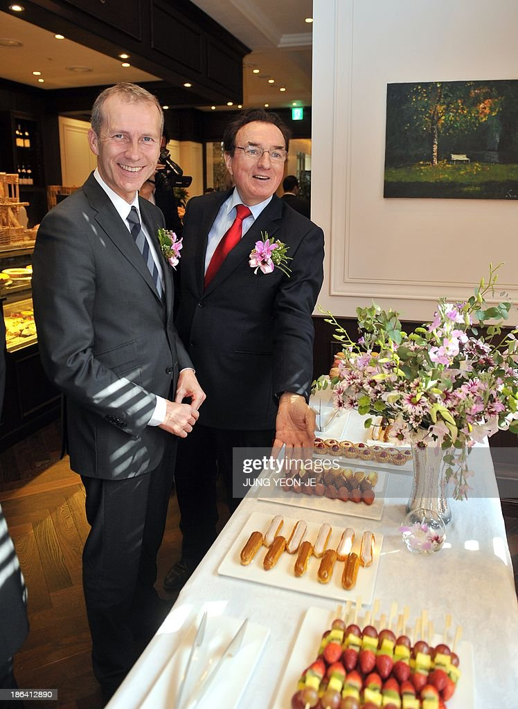 Louis Le Duff (R), founder and chairman of the French Le Duff cafe group, shows his bakery to French Junior Minister for Agriculture, Agribusiness and Forest Guillaume Garot (L) during an opening ceremony to launch its first shop in South Korea in Seoul on October 31, 2013. The French Le Duff cafe group opened its first Brioche Doree outlet in South Korea, looking to carve a quality niche in a lucrative but seemingly saturated coffee-bakery market.