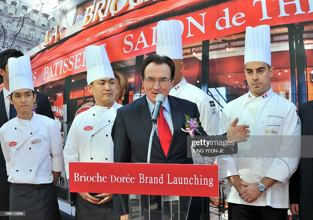 Louis Le Duff (C), founder and chairman of the French Le Duff cafe group, speaks during an opening ceremony to launch the company's first shop in South Korea in Seoul on October 31, 2013. The French Le Duff cafe group opened its first Brioche Doree outlet in South Korea, looking to carve a quality niche in a lucrative but seemingly saturated coffee-bakery market. At background, a poster of the company.