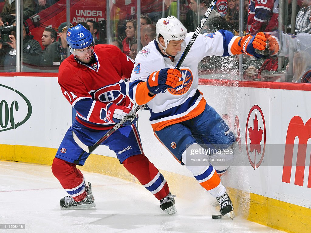 Louis Leblanc #71 of the Montreal Canadiens and Mark Eaton #4 of the New York Islanders battle along the boards for a loose puck during the NHL game on March 17, 2012 at the Bell Centre in Montreal, Quebec, Canada.