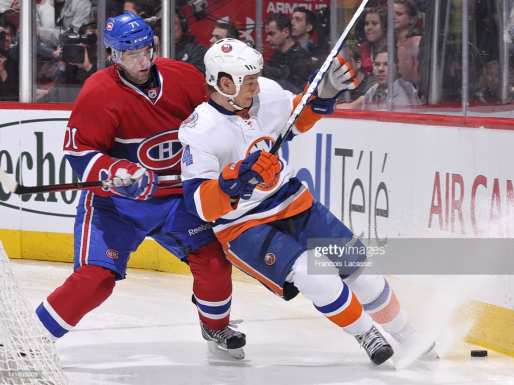 Louis Leblanc #71 of the Montreal Canadiens and Mark Eaton #4 of the New York Islanders battle for a loose the puck along the boards during the NHL game on March 17, 2012 at the Bell Centre in Montreal, Quebec, Canada.