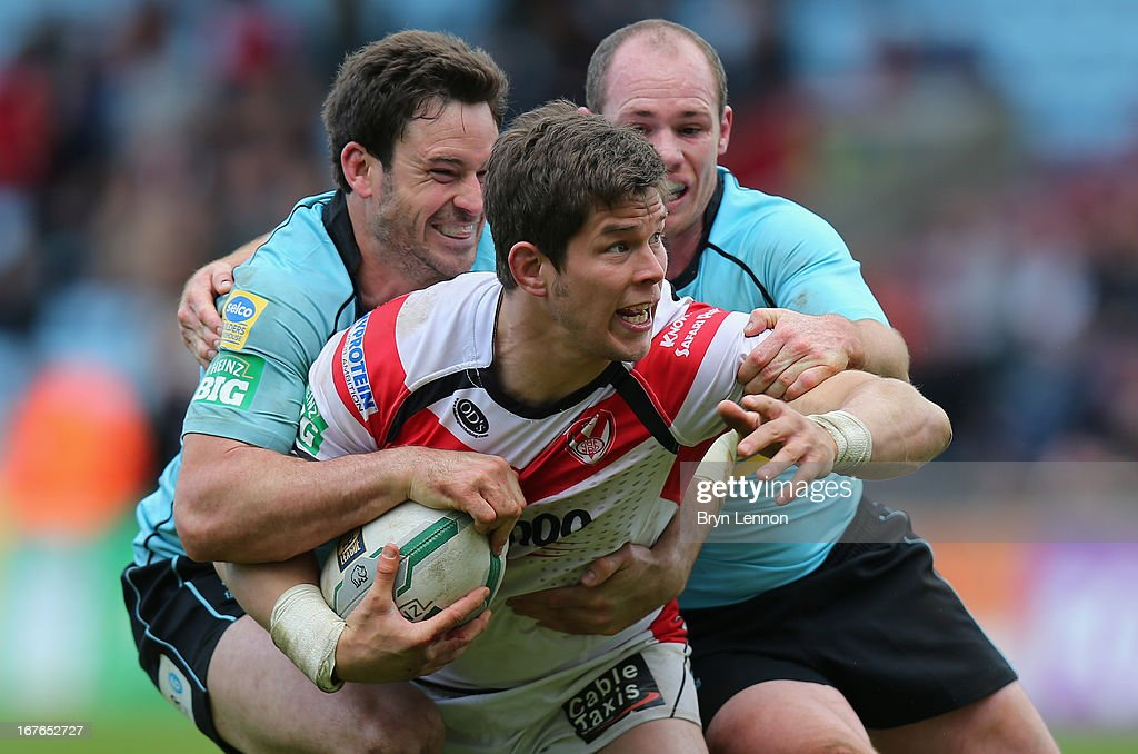 Louis McCarthy-Scarsbrook of St Helens is tackled by Chris Bailey and Ben Fisher during the Super League match between London Broncos and St Helens at Twickenham Stoop on April 27, 2013 in London, England.