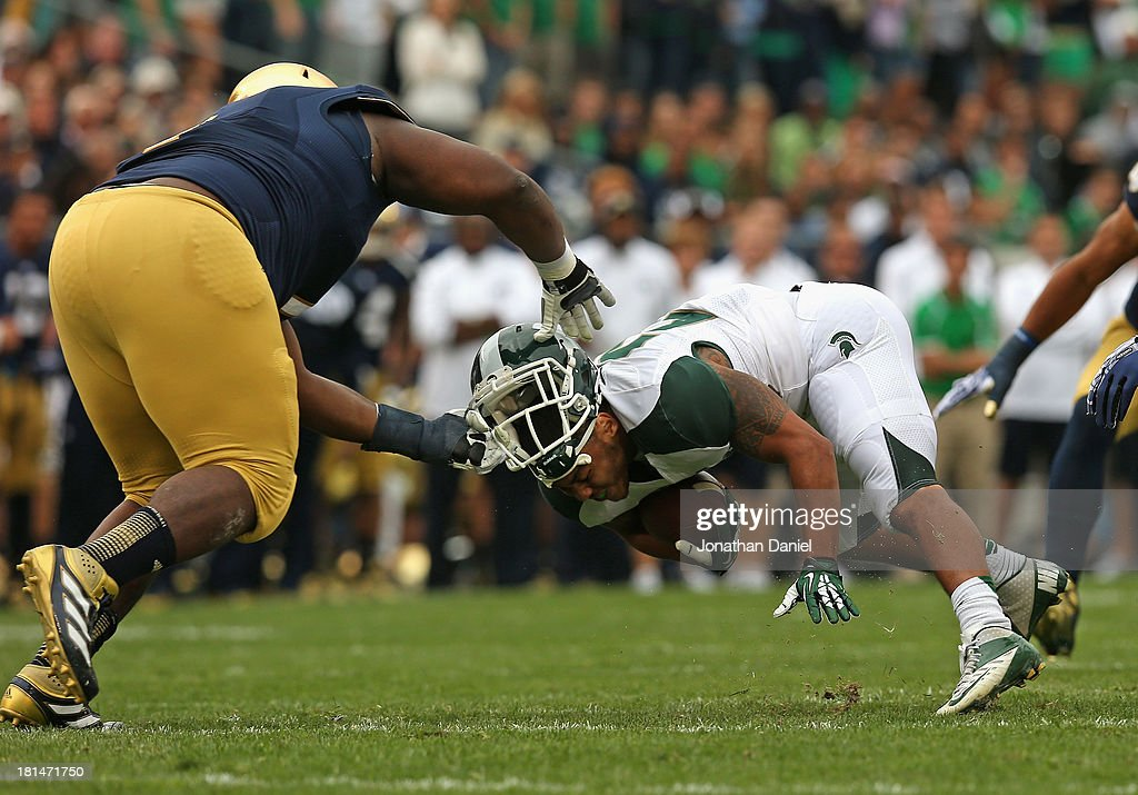 Louis Nix III #1 of the Notre Dame Fighting Irish pulls the helmet off of Nick Hill #20 of the Michigan State Spartans at Notre Dame Stadium on September 21, 2013 in South Bend, Indiana.