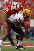 Louis Nzegwu of the Wisconsin Badgers drops Cameron Marshall of the Arizona State Sun Devils at Camp Randall Stadium on September 18 2010 in Madison...