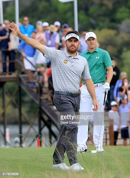 Louis Oosthuizen of South Africa and Jordan Spieth of the United react to the tee shot of Spieth on the 13th hole during the round of 16 in the World...