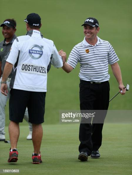 Louis Oosthuizen of South Africa celebrates his caddie Wynand Stander after holing a birdie putt on the 18th green to help his team win the proam...