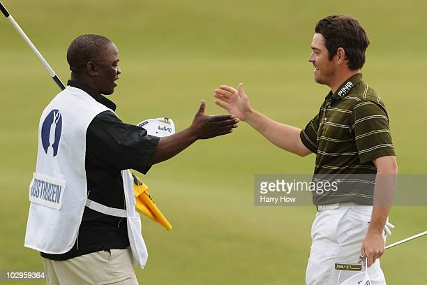 Louis Oosthuizen of South Africa celebrates his sevenstroke victory with his caddie Zack Rasego in the final round of the 139th Open Championship on...