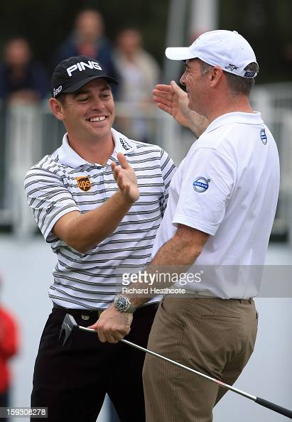 Louis Oosthuizen of South Africa celebrates with amateur partner Colin Ledworth of England as he holes a birdie putt on the 18th green to take the...