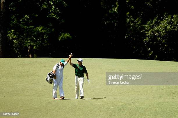 Louis Oosthuizen of South Africa celebrates with his caddie Wynand Stander after making an albatross on the second hole during the final round of the...