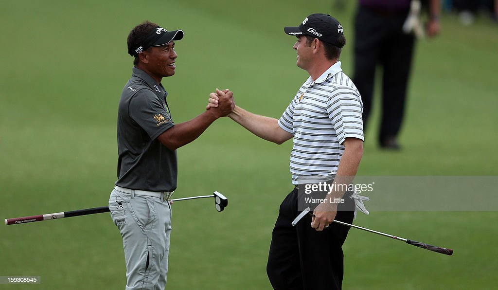 Louis Oosthuizen of South Africa celebrates with Thongchai Jaidee of Thailand after holing a birdie putt on the 18th green to help his team win the pro-am competition during the second round of the Volvo Golf Champions at Durban Country Club on January 11, 2013 in Durban, South Africa.
