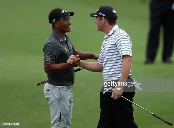 Louis Oosthuizen of South Africa celebrates with Thongchai Jaidee of Thailand after holing a birdie putt on the 18th green to help his team win the...