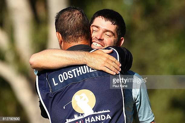 Louis Oosthuizen of South Africa embraces his caddie Wynard Stander after winning the 2016 Perth International at Karrinyup GC on February 28 2016 in...