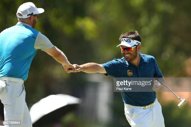 Louis Oosthuizen of South Africa knuckles Adam Bland of Australia as they walk back to the shoot out tee in match eighteen of the match play during...