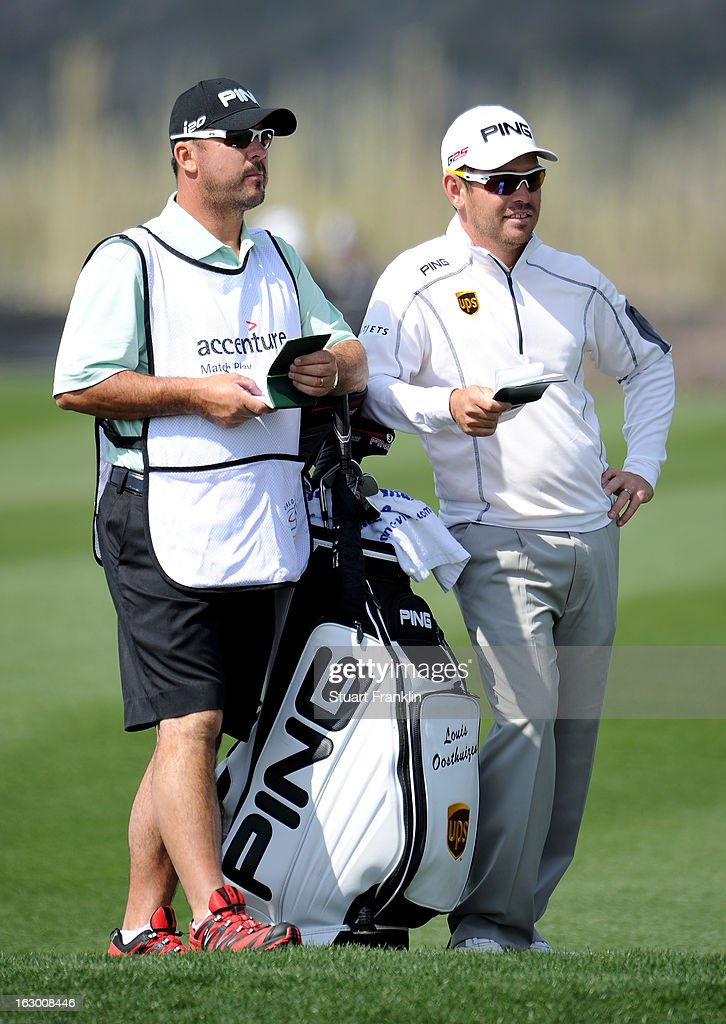 Louis Oosthuizen of South Africa looks on with his caddie Wynand Stander (L) during the second round of the World Golf Championships - Accenture Match Play at the Golf Club at Dove Mountain on February 22, 2013 in Marana, Arizona.