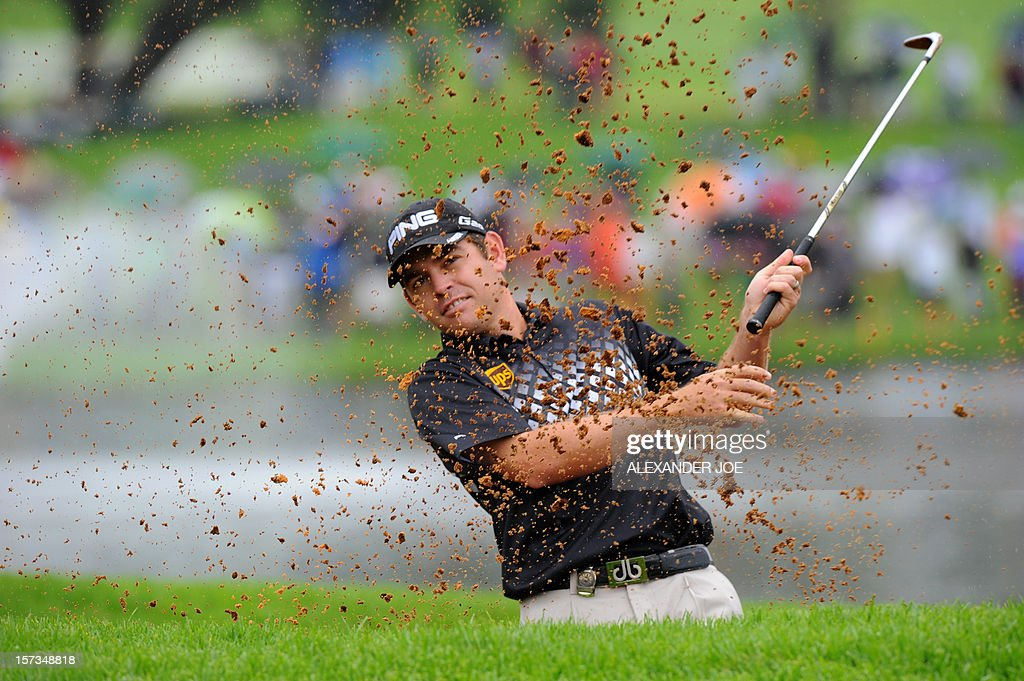 Louis Oosthuizen of South Africa plays a shot out of a bunker on the 18th during the 2012 Nedbank Golf Challenge in Sun City on December 2 ,2012.. AFP PHOTO / Alexander Joe