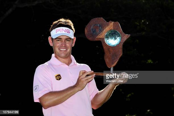 Louis Oosthuizen of South Africa poses with the trophy after winning the Africa Open after a three way playoff against Chris Wood of England and...