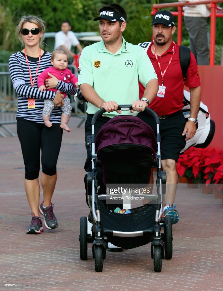 Louis Oosthuizen of South Africa pushes a pram as he walks with his wife Nel-Mare Oosthuizen and caddie Wynand Stander following the second round of the WGC - HSBC Champions at the Sheshan International Golf Club on November 1, 2013 in Shanghai, China.