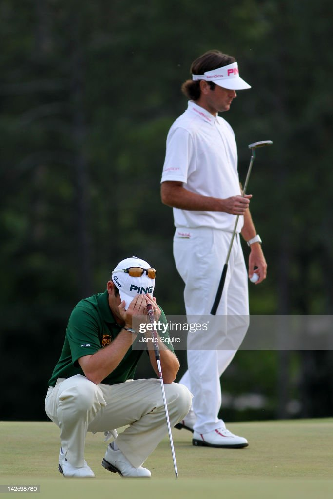 Louis Oosthuizen (L) of South Africa reacts after missing a putt on the 18th hole of regulation as Bubba Watson of the United States walks by during the final round of the 2012 Masters Tournament at Augusta National Golf Club on April 8, 2012 in Augusta, Georgia.