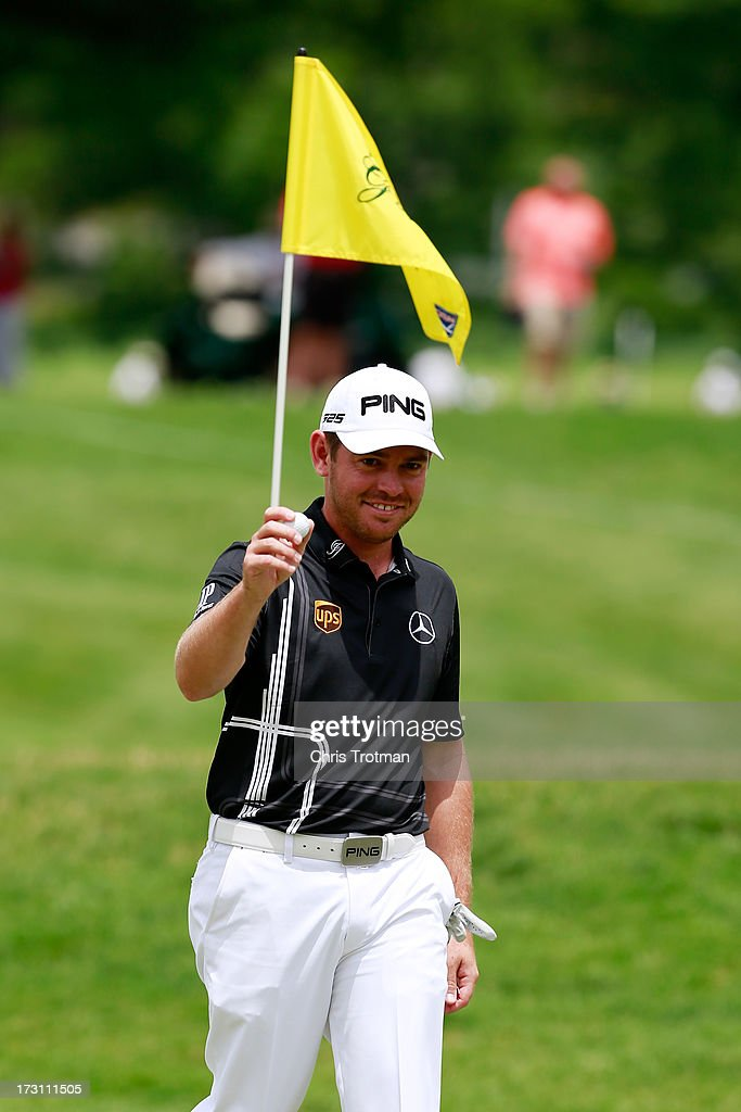 Louis Oosthuizen of South Africa reacts after pulling the ball out of the hole following and eagle on the second hole during the final round of the Greenbrier Classic at the Old White TPC on July 7, 2013 in White Sulphur Springs, West Virginia.
