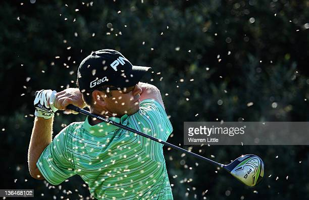 Louis Oosthuizen of South Africa tees off on the 12th hole as he is surrounded by flying ants during the second round of the Africa Open at East...