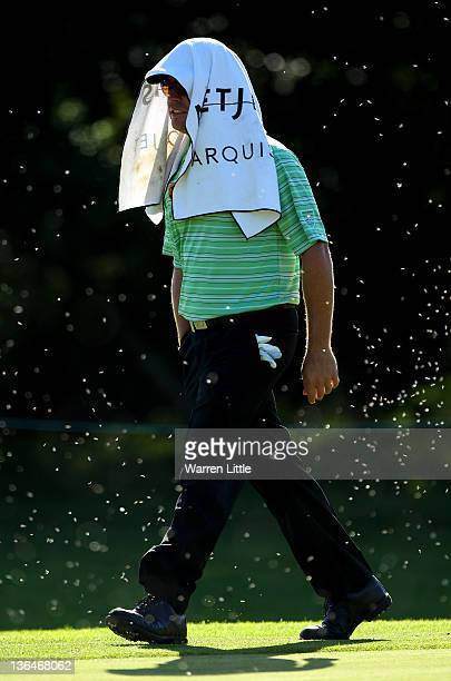 Louis Oosthuizen of South Africa uses his towel to hide from flying ants during the second round of the Africa Open at East London GC on January 6...