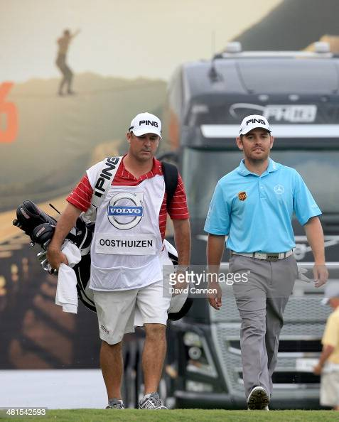 Louis Oosthuizen of South Africa walks with his caddie after hitting his tee shot at the par 4 18th hole during the first round of the 2014 Volvo...