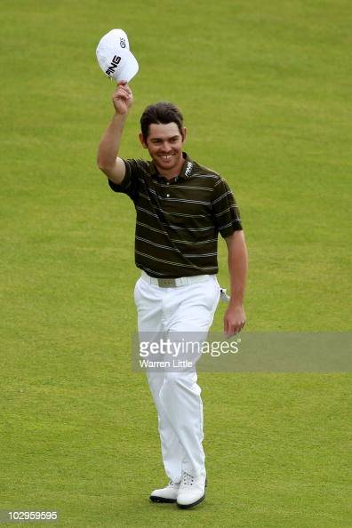 Louis Oosthuizen of South Africa waves to the crowd as he walks up the 18th fairway during the final round of the 139th Open Championship on the Old...