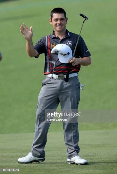 Louis Oosthuizen of South Africa waves to the crowd on the 18th green after sealing his victory with a birdie during the final round of the 2014...