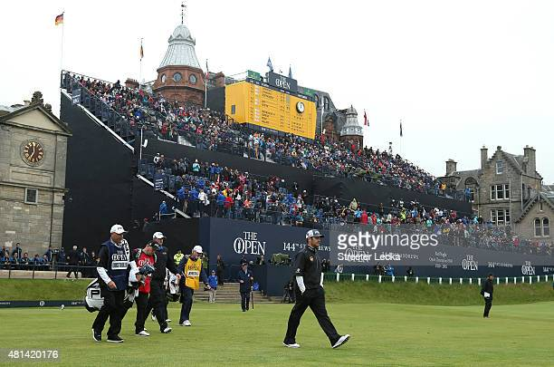 Louis Oosthuizen of South Africa Zach Johnson of the United States and Marc Leishman of Australia walk off the 1st tee with their caddies during the...