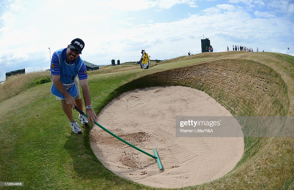 Louis Oosthuizen of South Africa's caddie Wynand Stander rakes a bunker ahead of the 142nd Open Championship at Muirfield on July 16, 2013 in Gullane, Scotland.