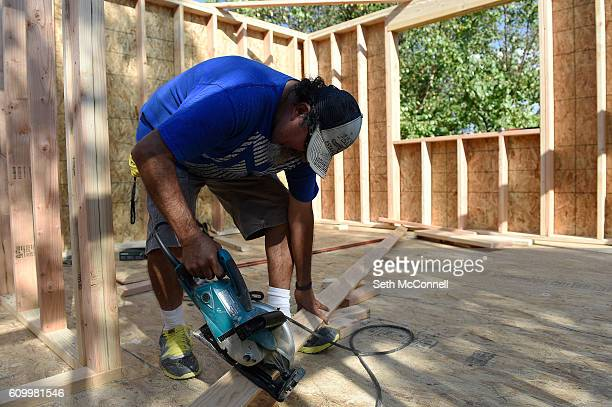 Louis Ortiz Sr uses a saw to cut a piece of 2x4 as he works on a second story addition to his home on Mildred Dr in Northglenn Colorado on September...