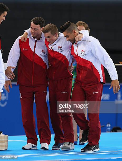 Louis Smith and Kristian Thomas of England help the injured Sam Oldham receive his gold medal during the medal ceremony of the Gymnastics Artistic...