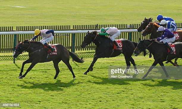 Louis Steward riding Bronze Angel win The Betfred Cambridgeshire at Newmarket racecourse on September 27 2014 in Newmarket England