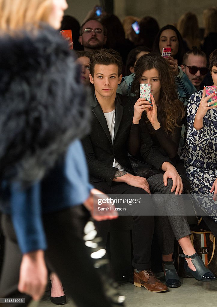 Louis Tomlinson of One Direction (L) and Eleanor Calder attend the Topshop Unique show at the Tate Modern during London Fashion Week Fall/Winter 2013/14 on February 17, 2013 in London, England.