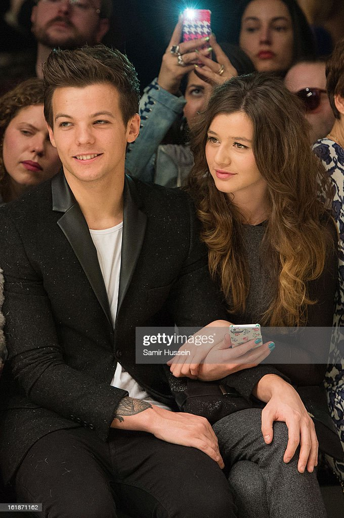 Louis Tomlinson of One Direction and Eleanor Calder attend the Topshop Unique show at the Tate Modern during London Fashion Week Fall/Winter 2013/14 on February 17, 2013 in London, England.