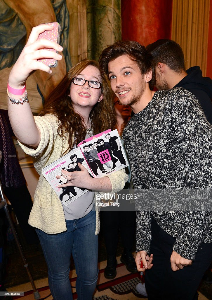 <a gi-track='captionPersonalityLinkClicked' href=/galleries/search?phrase=Louis+Tomlinson&family=editorial&specificpeople=7235196 ng-click='$event.stopPropagation()'>Louis Tomlinson</a> of One Direction poses for a picture with a fan as he attends the book signing of One Direction's new book 'Where We Are' held at Alexandra Palace on November 18, 2013 in London, England.