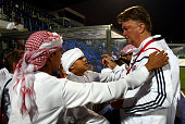 Louis van Gaal head coach of Bayern Muenchen signs autographs during the FC Bayern Muenchen training session at the Al Nasr training ground on...
