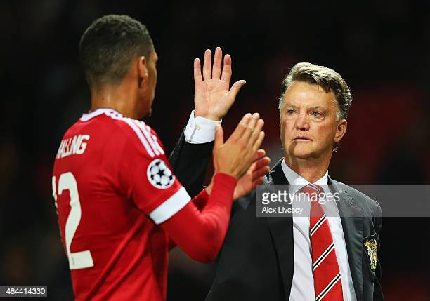 Louis van Gaal manager of Manchester United celebrates victory with Chris Smalling after the UEFA Champions League Qualifying Round Play Off First...