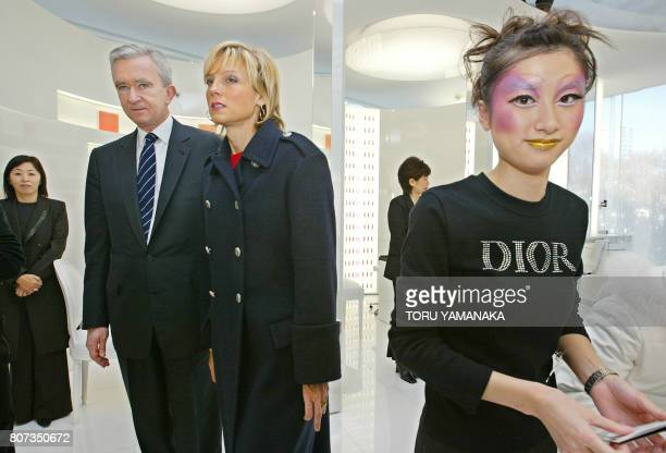 Louis Vuitton Moet Hennessy president Bernard Arnault and his wife Helene Arnault walk past a saleswoman as they look around the cosmetics floor...