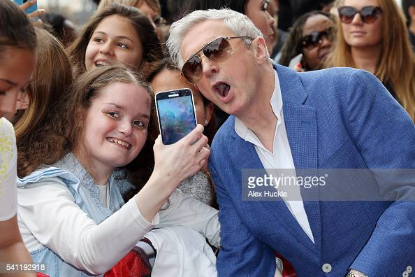 Louis Walsh poses for selfies with fans as he attends the X Factor Auditions on June 19 2016 in London England