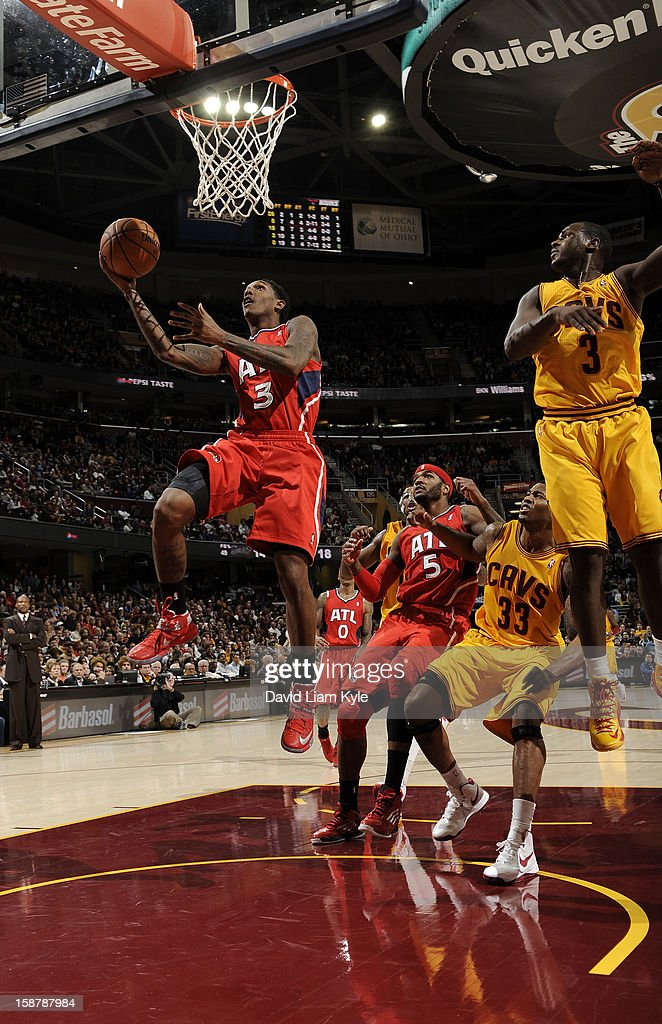 Louis Williams #3 of the Atlanta Hawks goes up for the shot against Alonzo Gee #33 and Dion Waiters #3 of the Cleveland Cavaliers at The Quicken Loans Arena on December 28, 2012 in Cleveland, Ohio.